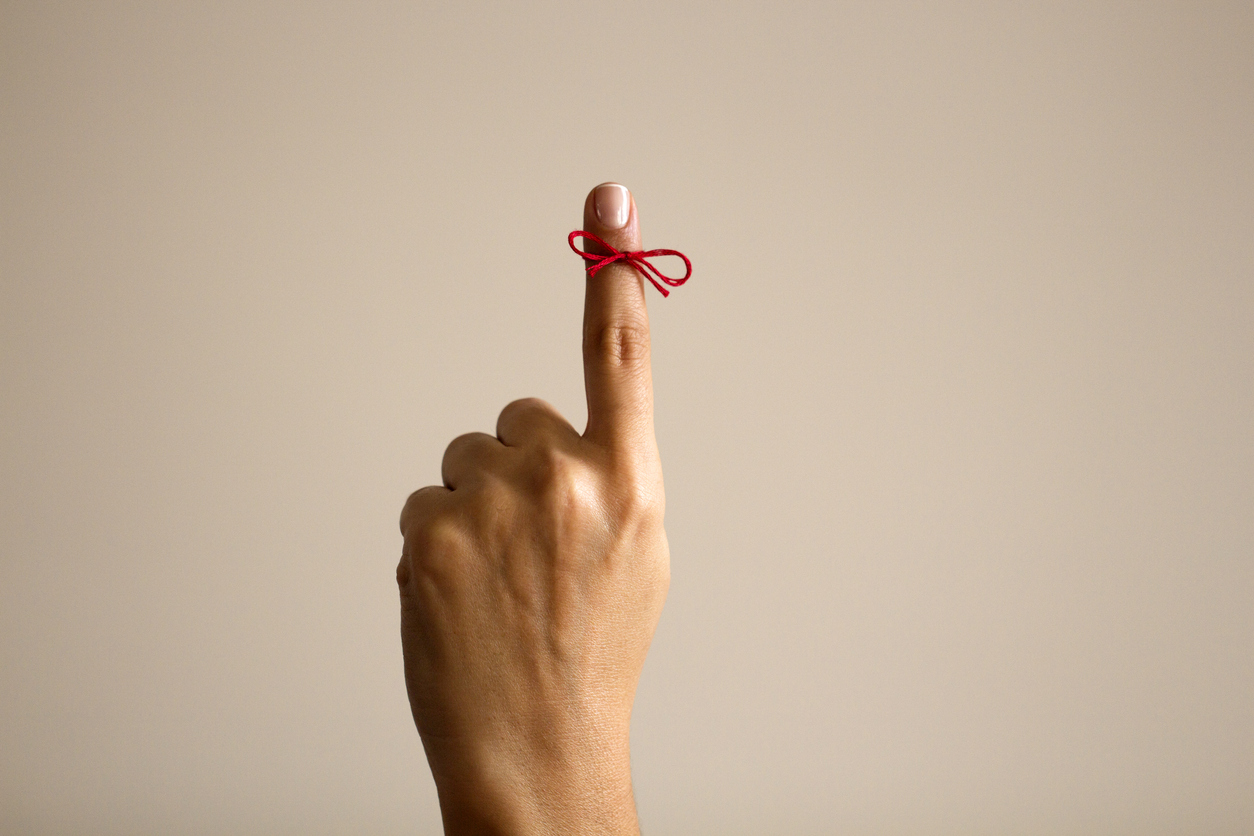 Red string tied in a ribbon on index finger
